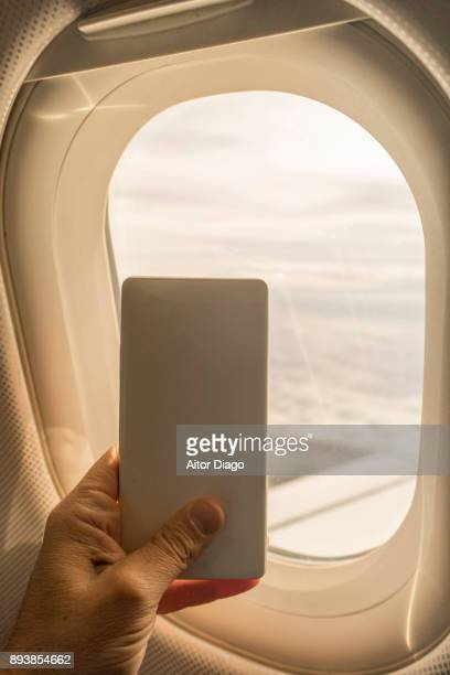 Flying in an Aeroplane. Hand holding an smart phone close to the window. Back view of the phone. The back camera is pointing out to the holder of the phone.