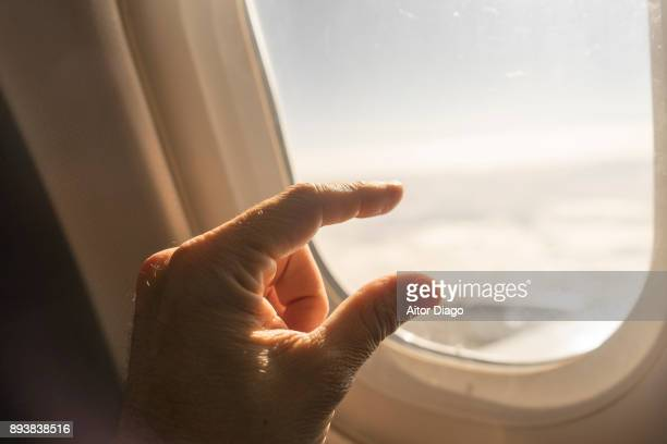 flying in an aeroplane. hand measuring something. - human finger stock photos and pictures