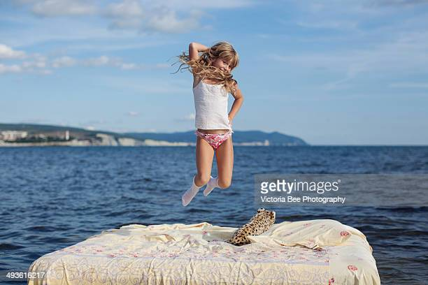 flying jump girl in blue sea - pants stock photos and pictures