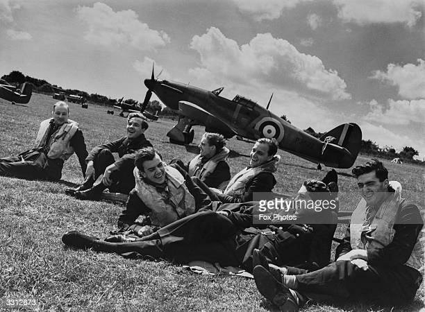A group of fighter pilots from the 32nd Squadron at the RAF Fighter Squadron HQ at Hawkinge Kent relax on the grass Left to right R F Smythe K R...