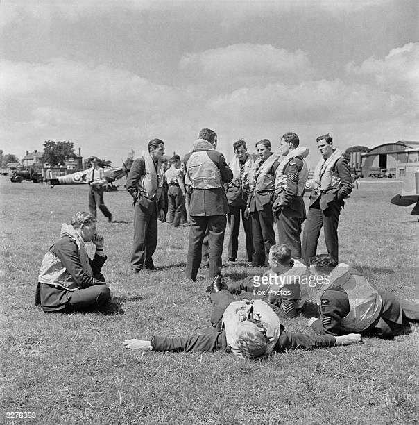 An RAF pilot rests on the grass on his return from combat at Hawkinge Airport in Kent