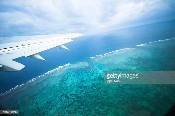 Flying over coral reef and blue tropical water