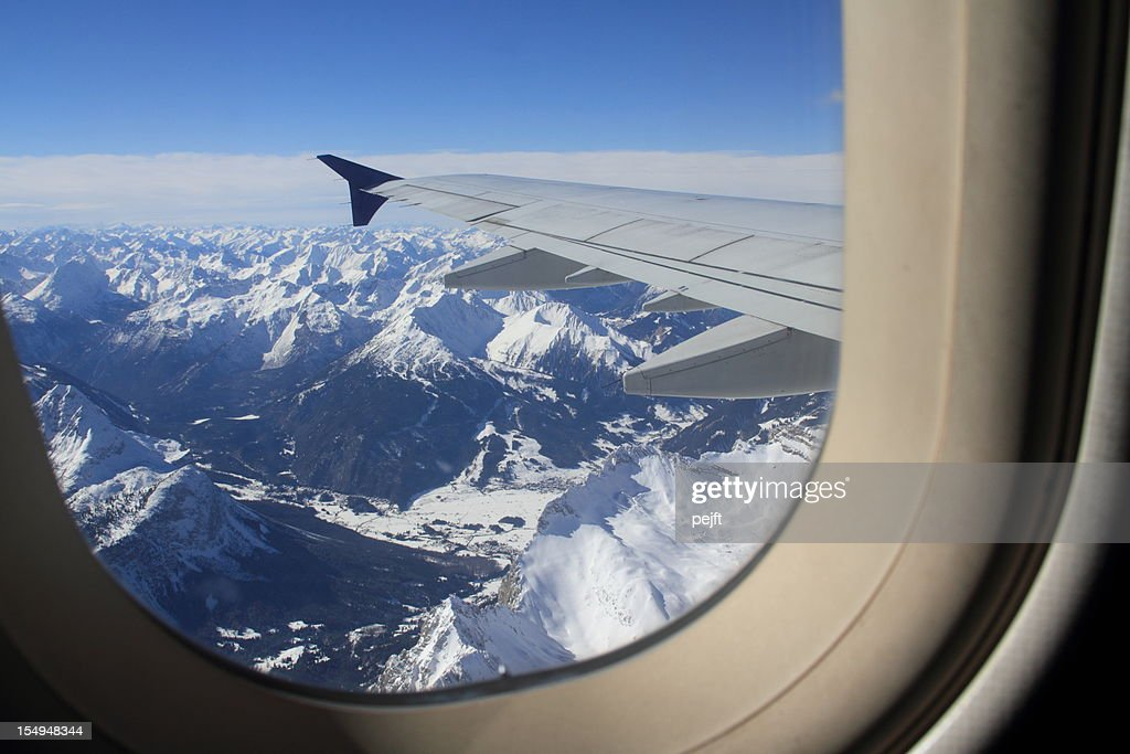 Flying over snow covered Austrian Alps mountain peaks : Stock Photo