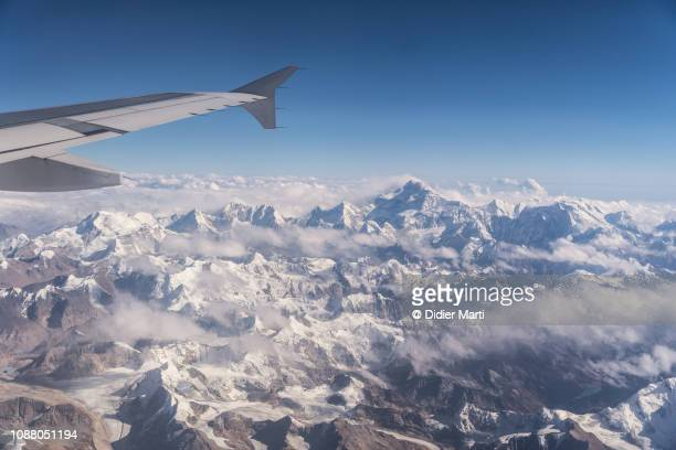 flying over the himalayas between nepal and tibet with the kangchenjunga mountain in the background - himalaya photos et images de collection