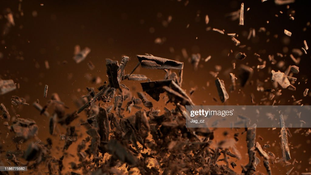 Flying pieces of crushed chocolate pieces : Stock Photo