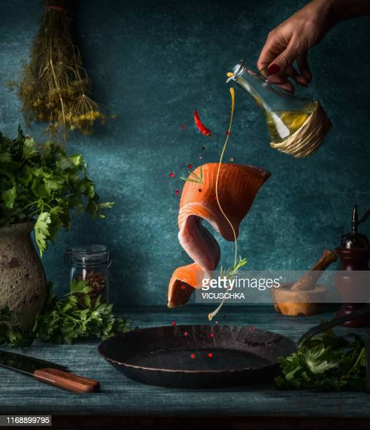 flying salmon fillet with herbs, spices and female hand with pouring olives oil - fliegen stock-fotos und bilder