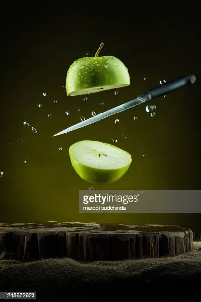 flying slices of green apple with knife - pointu photos et images de collection