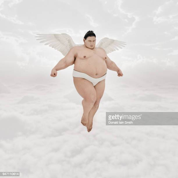 flying sumo hovers with tiny angel wings - sumo wrestling stock pictures, royalty-free photos & images