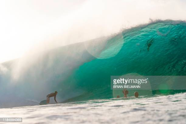 Flyn Novak from Hawaii looks up on the face of the waves as he surfs a big day at Pipeline on the North Shore of Oahu, Hawaii on November 24, 2019. /...