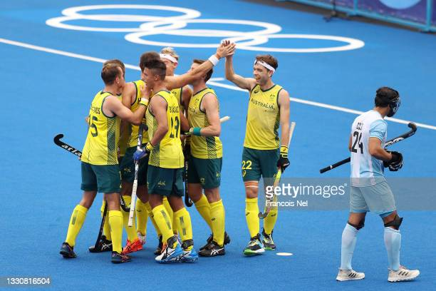 Flynn Andrew Ogilvie and Tim Brand of Team Australia celebrate their fifth goal scored with teammates during the Men's Preliminary Pool A match...