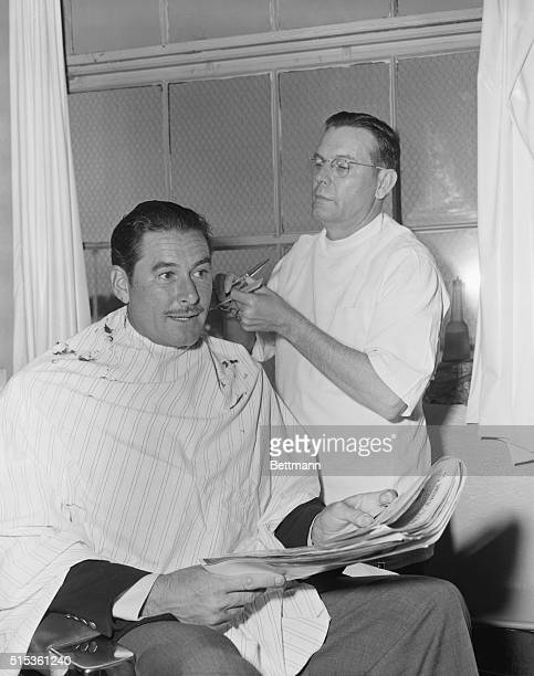 Errol Flynn stops at the Miami International Airport's barber shop just long enoughfor a haircut before boarding a plane for Nassau He is back from...