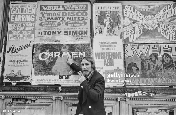 Flyposter Terry 'The Pill' Slater with a wall of posters, London, UK, 15th December 1973. They are advertising such acts as Argent, Carmen, Billy...
