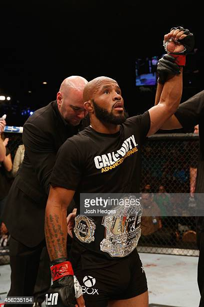 Flyweight champion Demetrious Johnson celebrates after his win over Chris Cariaso after their flyweight championship fight during the UFC 178 event...