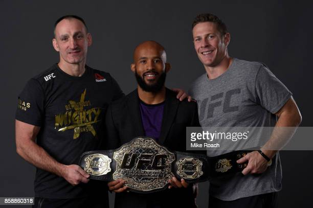 UFC flyweight champion Demetrious Johnson poses for a portrait backstage with his coaches after his victory over Ray Borg during the UFC 216 event...