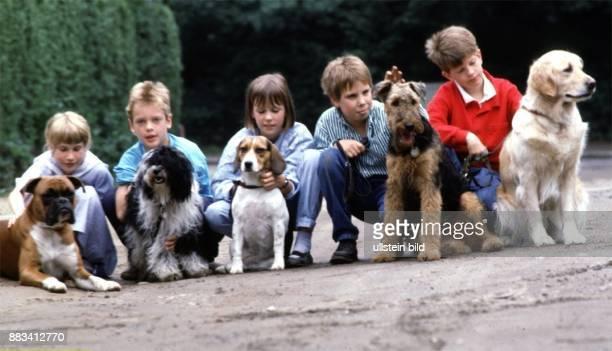 Fünf Kinder hocken neben ihren Hunden