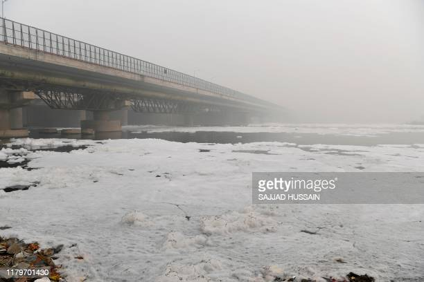 Foam is seen floating along the Yamuna river near a bridge amidst heavy smog conditions, in New Delhi on November 3, 2019. - India's capital New...