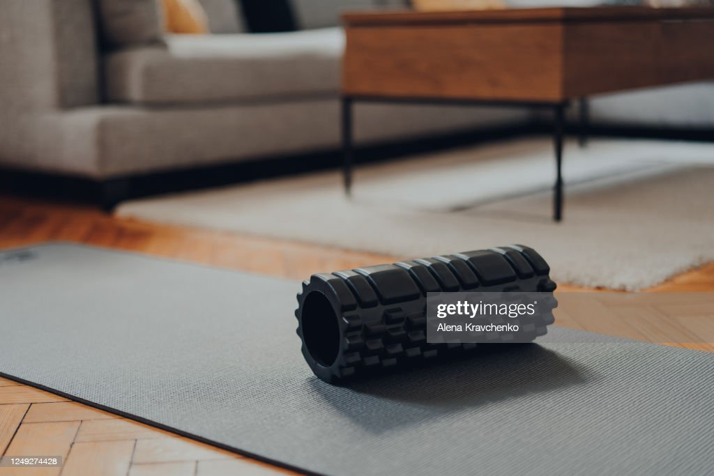 Foam roller and a fitness mat within modern living space, selective focus. : Stock Photo