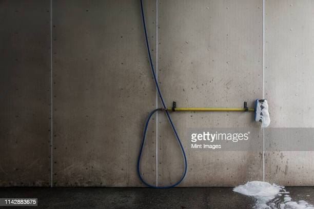 foaming brush with hose in car wash - car wash brush stock photos and pictures