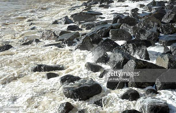foamy water crashing onto black rocks - lyn holly coorg stock pictures, royalty-free photos & images