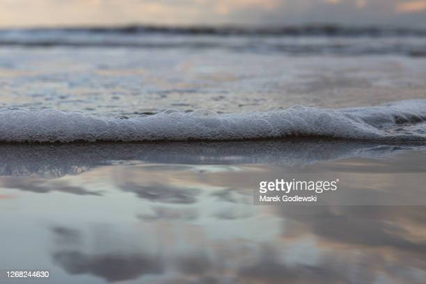foamy wave, sky reflection in the water, curracloe, co. wexford, ireland - wet stock pictures, royalty-free photos & images