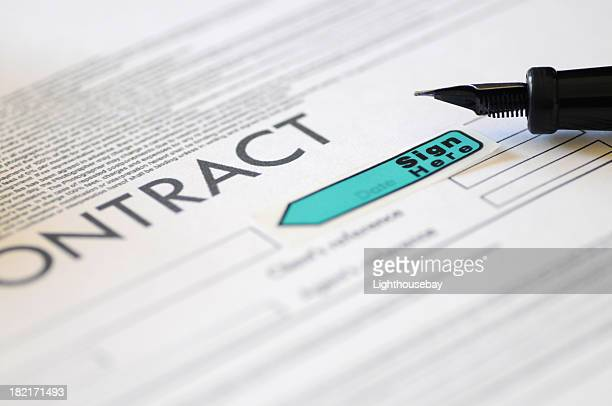 focus of tip of fountain pen resting on a contract - deed stock photos and pictures