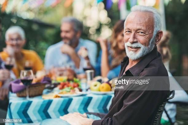 nadruk op een glimlachende hogere mens op een familieviering - gemengde leeftijdscategorie stockfoto's en -beelden