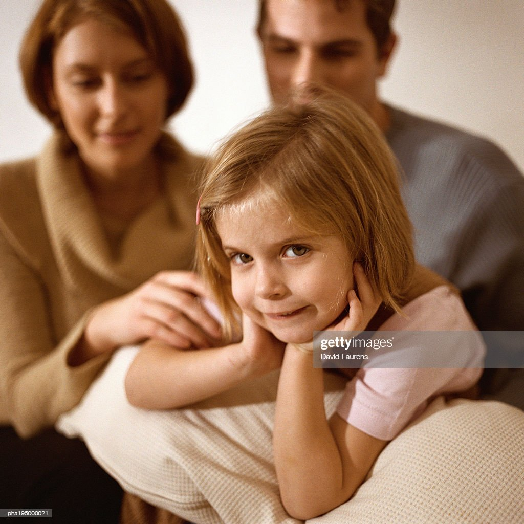 Focus on daughter looking at camera, parents behind her. : Stockfoto