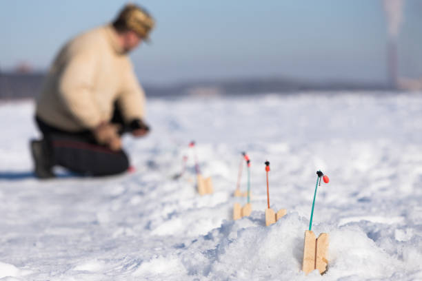 Focus On Fishing Nets For Ice Fishing, Blurred Fisherman Checks Fishing Rod, Sunny Winter Frosty Day