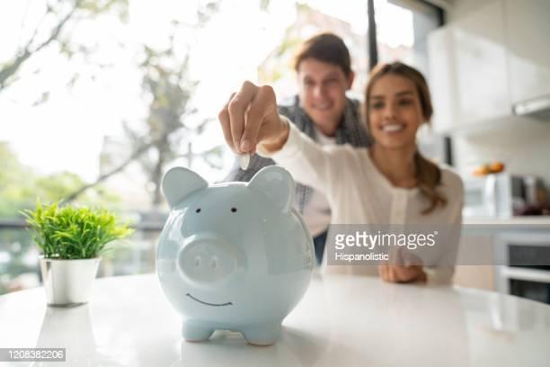 focus on foreground of latin american young couple saving coins into piggy bank - economia imagens e fotografias de stock