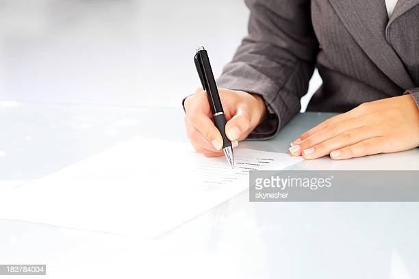 Focus on human hand - woman signing a contract.