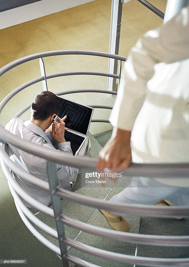Focus on man sitting on stairs with cell phone and laptop computer, person walking up stairs in foreground, blurred. : ストックフォト