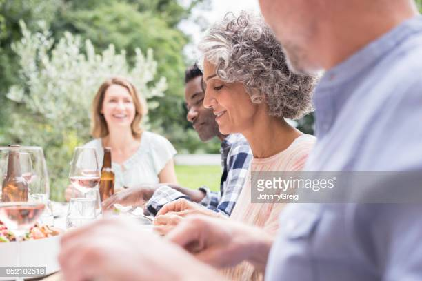 Focus on mature woman with grey curly hair having dinner
