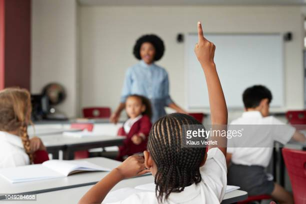 focus on schoolgirls raised hand in classroom with teacher - classroom stock pictures, royalty-free photos & images