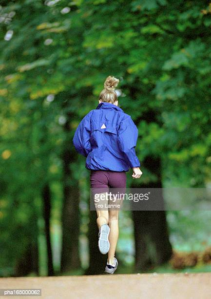 Focus on woman in sports clothes running, full length, trees in background
