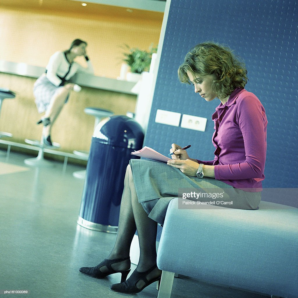 Focus on woman seated on bench looking down at paper, full length, woman seated on stool in background. : Stockfoto