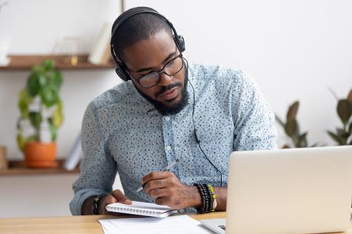 Focused african businessman in headphones writing notes watching webinar 1150384596