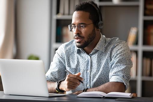 Focused african businessman wear headphones study online watching webinar 1203044233