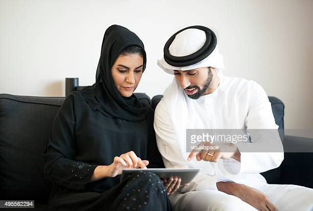 Focused Arab Couple Discussing Things Using Digital Tablet