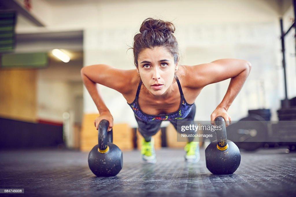 Focused athlete doing push-ups on kettlebells in gym : Photo