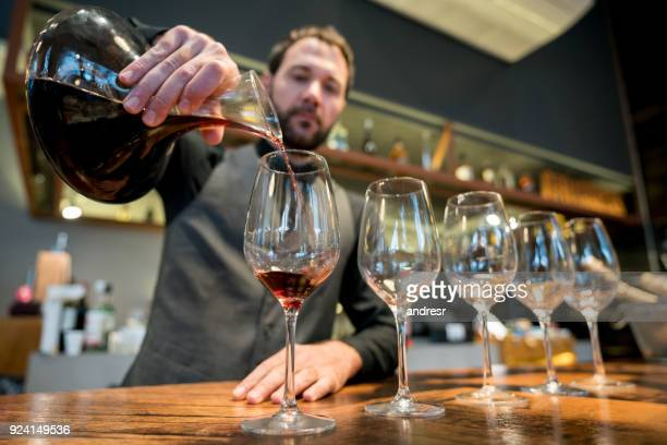 Focused bar tender serving wine from a decanter at a restaurant