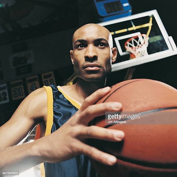 Focused Basketball Player Holding the Ball on a Basketball Court