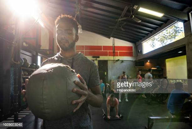 focused black man holding an exercise ball at the gym - hispanolistic stock photos and pictures