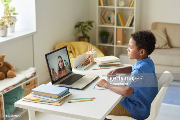 focused black schoolboy with curly hair sitting at desk and using laptop while listening to tutor during video conference - tutor stock pictures, royalty-free photos & images