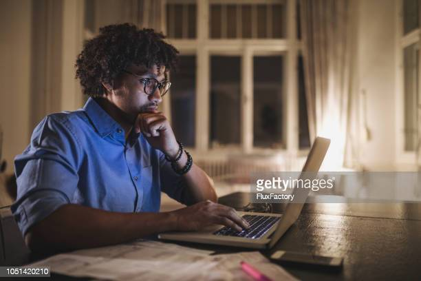 focused black student working on his laptop computer - educational exam stock pictures, royalty-free photos & images