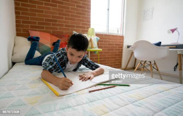 Konzentrierte sich der Junge seine Hausaufgaben liegen auf seinem Bett mit Farben und ein notebook