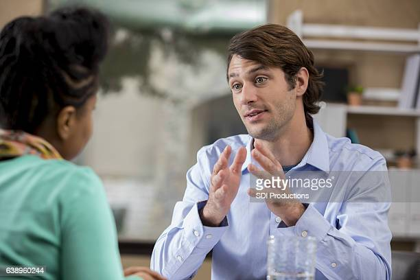 focused businessman discusses issue with client - mid adult stock pictures, royalty-free photos & images