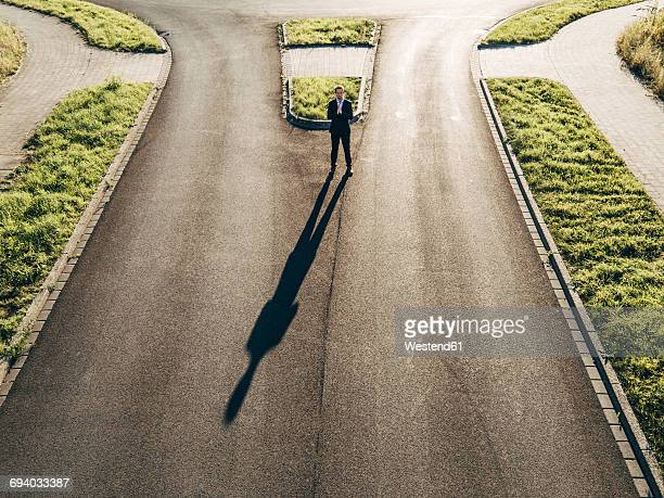 Focused businessman standing on road