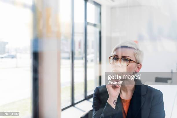 Focused businesswoman looking at glass pane in office