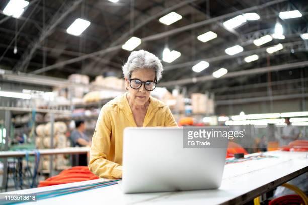 uma mulher de negócios focalizada que usa o portátil e que trabalha em uma fábrica - ciência e tecnologia - fotografias e filmes do acervo