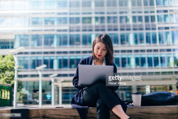 focused businesswoman working with laptop in the financial district - on the move stock pictures, royalty-free photos & images